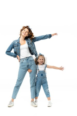 Photo for Daughter and mother in denim outfits with outstretched hands isolated on white - Royalty Free Image