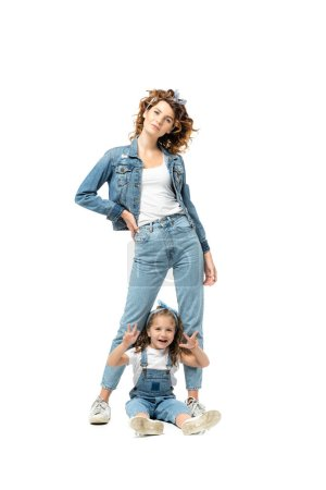 Photo for Mother and daughter in denim outfits posing isolated on white - Royalty Free Image
