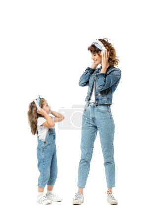 Photo pour Mother and daughter in denim outfits listening music in headphones and looking at each other isolated on white - image libre de droit