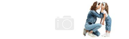 Photo pour Vue latérale de la mère et de la fille en tenue denim écoutant de la musique dans les écouteurs face à face isolé sur blanc, plan panoramique - image libre de droit