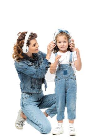 Photo pour Mère et fille en tenue denim écouter de la musique dans des écouteurs isolés sur blanc - image libre de droit