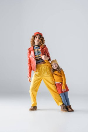 Photo pour Mother and daughter in colorful red and yellow outfits posing on grey background - image libre de droit