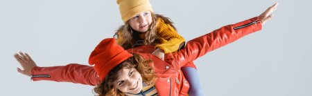 mother in colorful red and yellow outfit imitating plane with daughter on back isolated on grey, panoramic shot