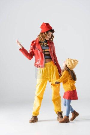 Photo pour Fille en tenue colorée rouge et jaune étreignant la jambe mère sur fond gris - image libre de droit
