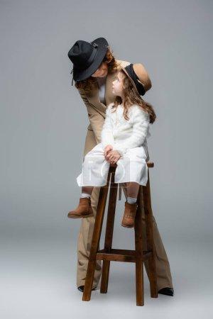Photo pour Elegant mother posing near daughter on chair on grey - image libre de droit