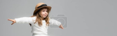 Photo for Elegant girl in hat with outstretched hands showing tongue isolated on grey, panoramic shot - Royalty Free Image