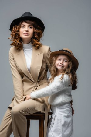 elegant mother and daughter in white and beige outfits posing on chair isolated on grey