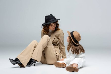 Photo pour Elegant mother and daughter in white and beige outfits and hats posing on floor on grey background - image libre de droit