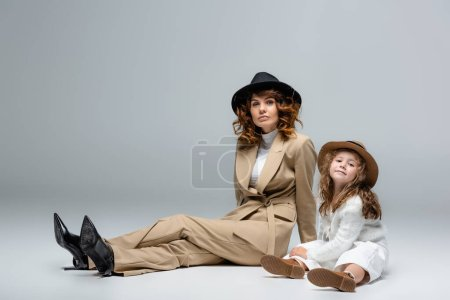 elegant mother and daughter in white and beige outfits and hats posing on floor on grey background