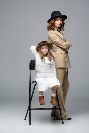 Photo pour Elegant mother and daughter in white and beige outfits and hats posing on chair on grey background - image libre de droit