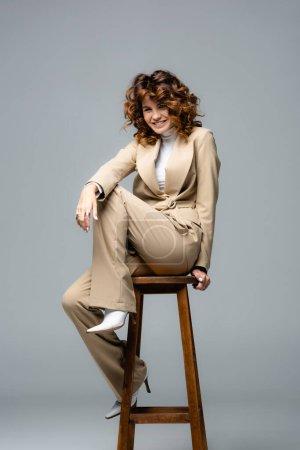 elegante Frau im beigen Anzug posiert auf Holzstuhl und lächelt auf grauem Hintergrund