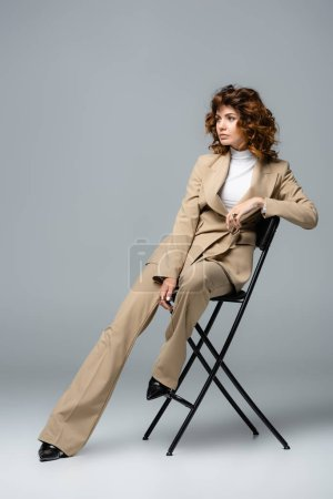 elegant woman in beige suit posing on chair on grey background