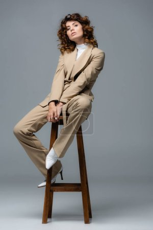elegant woman in beige suit posing on wooden chair on grey background