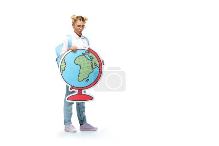 Photo for Full length view of amazed schoolgirl in eyeglasses holding paper cut globe while standing on white - Royalty Free Image