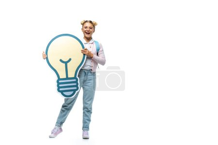 Photo for Full length view of excited schoolgirl in jeans holding paper cut light bulb and looking at camera on white - Royalty Free Image