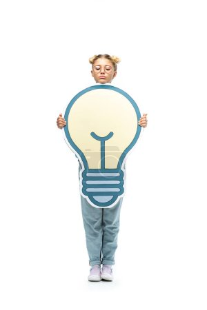 Photo for Full length view of schoolchild in jeans and eyeglasses holding paper cut light bulb on white - Royalty Free Image