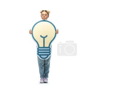 Photo pour Vue pleine longueur de l'écolière en jeans et lunettes tenant ampoule coupe papier sur blanc - image libre de droit