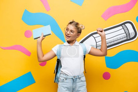 Photo for Excited schoolgirl in eyeglasses holding book and showing triumph gesture near paper pencil and colorful elements on yellow - Royalty Free Image