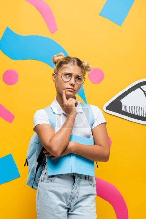 Photo for Thoughtful schoolgirl in eyeglasses looking away while holding book near paper pencil and colorful elements on yellow - Royalty Free Image