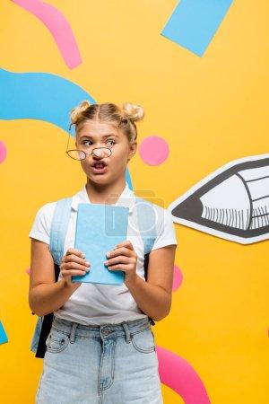 Photo pour Écolière perplexe en lunettes asymétriques tenant livre près du crayon de papier et des éléments colorés sur jaune - image libre de droit