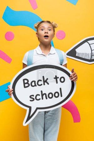 Photo pour Écolier choqué regardant la caméra tout en tenant bulle de parole avec retour à l'école lettrage sur fond jaune avec crayon en papier et des éléments colorés - image libre de droit