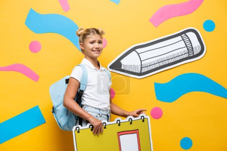 Photo pour Tense pupil with notebook maquette looking at camera on yellow background with paper cut pencil and colorful elements - image libre de droit