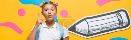 horizontal crop of shocked pupil pointing with finger while looking at camera near paper pencil and decorative elements on yellow
