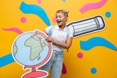 Photo pour Joyful schoolgirl holding globe maquette on yellow background with paper pencil and abstract elements - image libre de droit