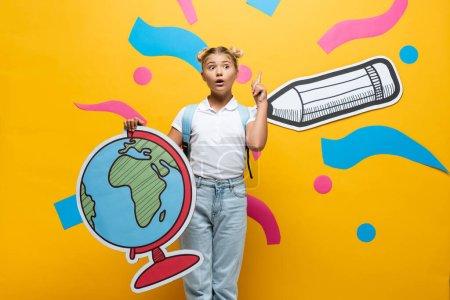 Photo pour Amazed schoolgirl showing idea gesture while holding globe maquette near paper pencil and colorful elements on yellow - image libre de droit