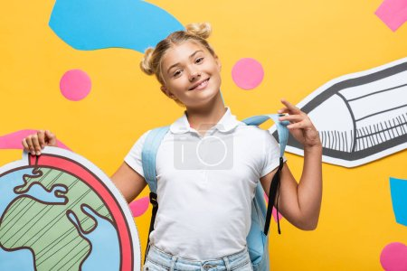 Photo pour Pleased schoolgirl holding globe maquette on yellow background with paper pencil and colorful elements - image libre de droit