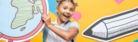 Photo pour Panoramic shot of excited schoolgirl holding maquette of globe on yellow background with paper elements and pencil - image libre de droit