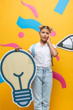 Foto de Impactada cara conmovedora de la pupila mientras sostiene la maqueta ligera de la burbuja en el fondo amarillo con elementos decorativos y lápiz de papel - Imagen libre de derechos