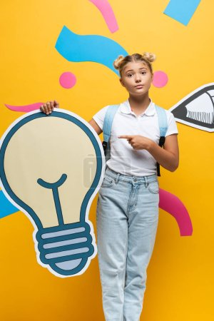 Photo for Schoolgirl with backpack pointing with finger at decorative light bulb near paper art on yellow background - Royalty Free Image