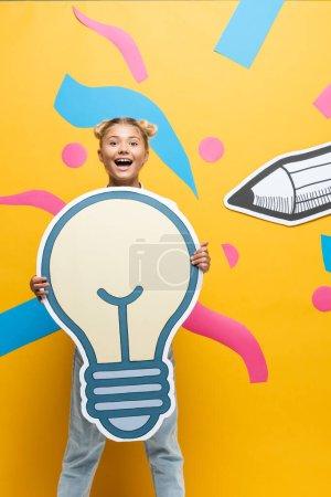 Photo pour Écolière excitée tenant une ampoule en papier à côté d'éléments en papier sur fond jaune - image libre de droit