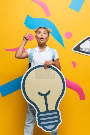 Umfassende Schülerin mit Idee, während sie dekorative Glühbirne in der Nähe von Papierkunst auf gelbem Hintergrund hält
