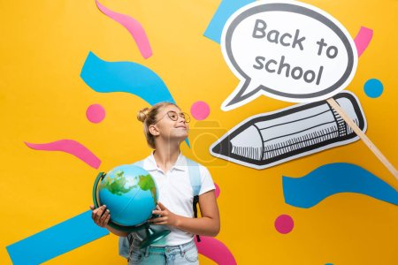 Schoolgirl in eyeglasses holding globe near paper elements with back to school lettering on speech bubble on yellow background