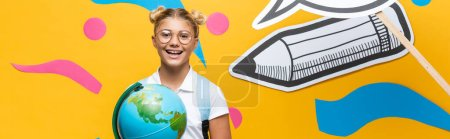 Horizontal image of schoolkid with globe looking at camera near paper craft on yellow background