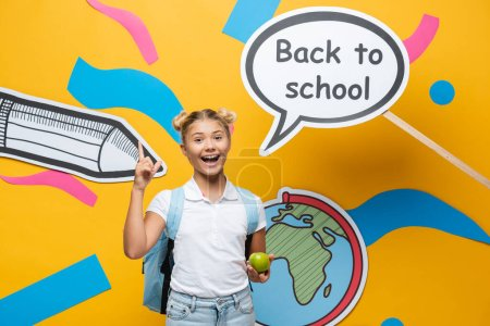 Schoolgirl with apple having idea near back to school lettering on speech bubble and paper art on yellow background