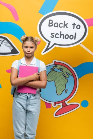 Skeptical schoolgirl holding laptop near speech bubble with back to school lettering and paper art on yellow background