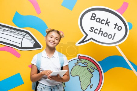 Schoolchild holding digital tablet near paper speech bubble with back to school lettering on yellow background