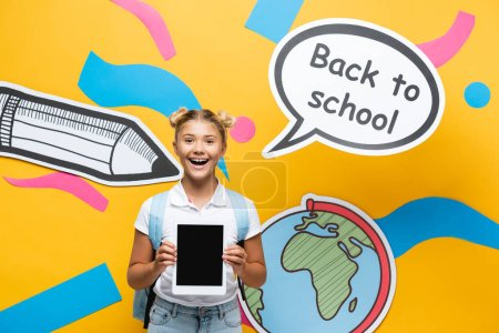 Photo pour Schoolkid holding digital tablet with blank screen near paper craft and speech bubble on yellow background - image libre de droit