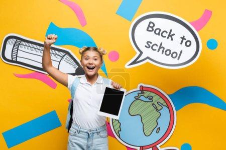 Photo pour Écolière tenant une tablette numérique et montrant un geste ouais près de la bulle d'expression et de l'art du papier sur fond jaune - image libre de droit