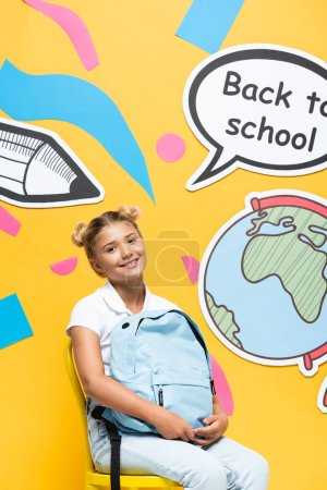 Schoolgirl holding backpack on chair near speech bubble with back to school lettering and paper art on yellow background