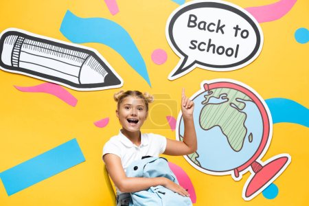 Schoolchild with backpack pointing at back to school lettering and paper elements on yellow background