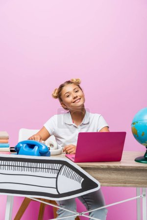 Photo for Child sitting near laptop, globe and paper art on desk on pink background - Royalty Free Image