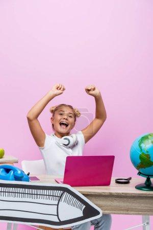 Écolier excité assis près d'un ordinateur portable, globe et papier art sur fond rose