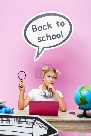 Pensive schoolgirl with magnifying glass near gadgets, books and paper art on pink background