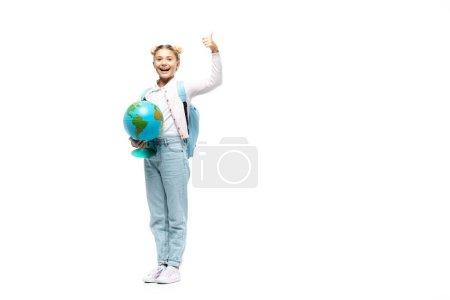 Photo for Schoolgirl showing thumb up while holding globe on white background - Royalty Free Image