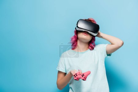 Photo for KYIV, UKRAINE - JULY 29, 2020: young woman with pink hair in vr headset with joystick on blue background - Royalty Free Image