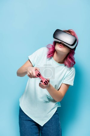 Photo for KYIV, UKRAINE - JULY 29, 2020: young woman with pink hair in vr headset playing video game with joystick on blue background - Royalty Free Image